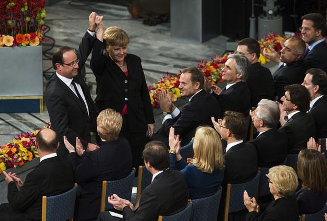 仏オランド大統領と独メルケル首相。2012年、欧州連合がノーベル平和賞を受賞したとき、手を掲げる2人 (Statsministerens kontor/Flickr)