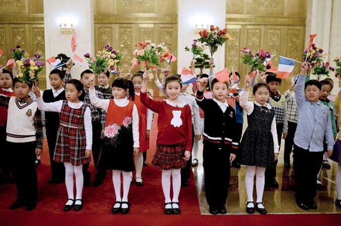 11月2日、北京の人民大会堂のセレモニー会場前で、フランスと中国の旗を振り、訪中している仏オランド大統領を待つ中国の子供たち。12月開催予定の国連気候変動パリ会議を前に、大統領は習近平国家主席に対して温暖化ガス排出の対策に積極姿勢を求めた。(STEPHANE DE SAKUTIN/AFP/Getty Images)