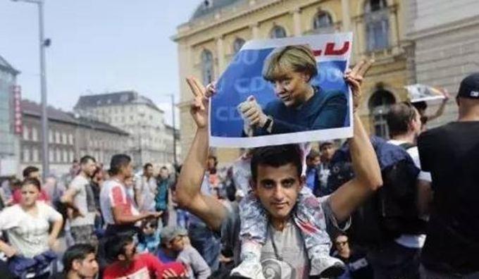 メルケル首相の写真を掲げて感謝の意を表すシリアの難民