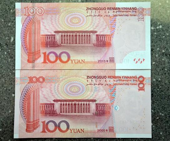 偽造防止加工が施されているという新100元札(写真上)、12日から流通が開始したが、翌日、国内の一部ATMで「偽札」と認識され利用できないと、国内メディアに報道されている。(STR/AFP/Getty Images)