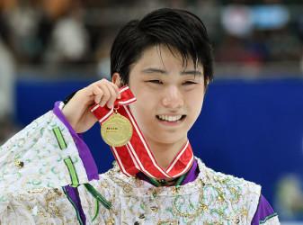 28日、グランプリシリーズ最終戦・NHK杯を制し、表彰台で優勝メダルを掲げて微笑む羽生結弦(TOSHIFUMI KITAMURA/AFP/Getty Images)