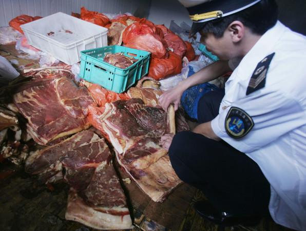 食肉を検査する北京健康監督研究所の職員 (Getty Images)