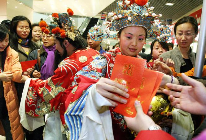 北京のショッピングモールで配られる従来の紅包 (STR/AFP/Getty Images)
