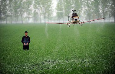 ドローンを使い農薬を散布するドローン操縦者(AFP/GettyImages)