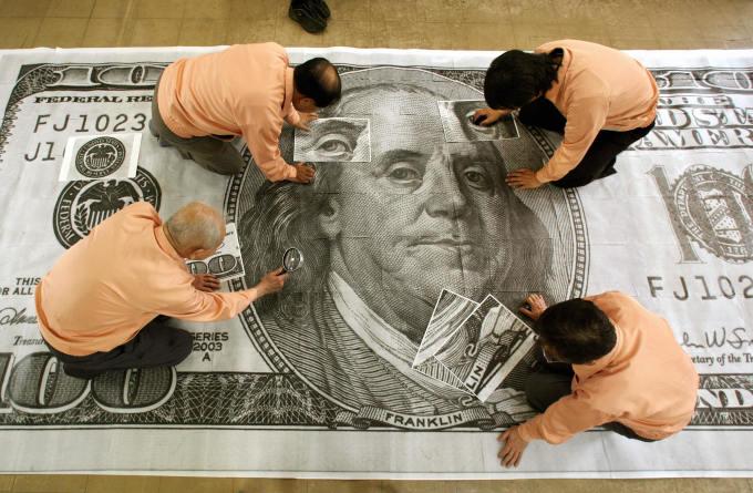 あるイベントで、北朝鮮で作られたとする偽100ドル札を400倍に拡大し、本物紙幣と見比べるスタッフ。本記事とは無関係 (KAZUHIRO NOGI/AFP/Getty Images)
