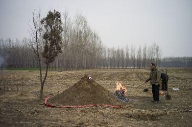 河北省のある自然葬による土の墓の前で、紙銭を焼く人。2015年4月1日の清明祭で(FRED DUFOUR/GettyImages)