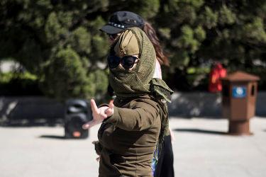 「党員であることが恥ずかしい」と多くの共産党員が考えている。社会には党のマイナスイメージが常識となった。写真は4月16日、北京の天安門広場で日よけのために顔を布で覆う観光客の女性(FRED DUFOUR/AFP/Getty Images)