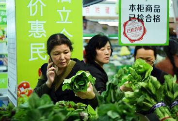 2016年4月、杭州のスーパーマーケットで葉野菜を選ぶ消費者(STR/GettyImages)