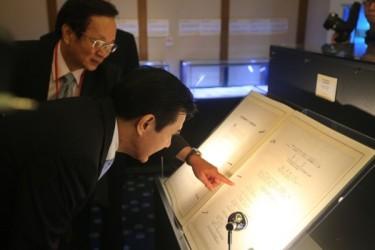 昨年7月7日に開催された国史館の抗戦勝利70年国際学術フォーラム開幕式に出席した馬英九総統(前)と国史館の呂芳上・館長(後)が、1945年日本政府が調印した連合国への降伏文書を閲覧した (中央社)
