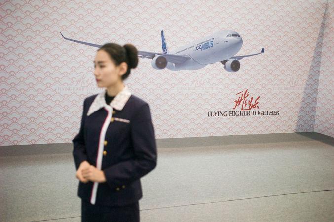 天津で、エアバス社の新機種を中国で展開するセレモニーが3月行われた。客人を迎えるコンパニオン(FRED DUFOUR/AFP/Getty Images)