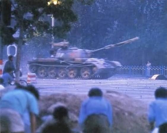 民主化を求めて天安門広場に集まった学生を中心とした一般人に向けて、共産党政権は戦車を配備し、丸腰の市民を無差別に虐殺した。写真は戦車の動きをうかがう学生ら(ネット写真)