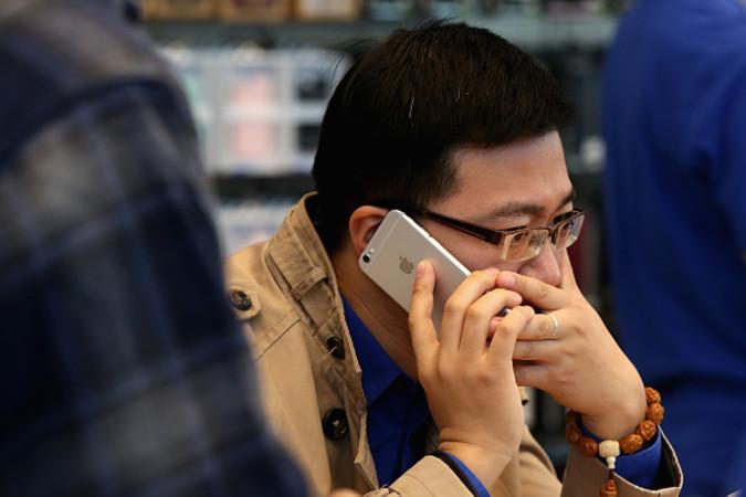 2014年10月北京のアップルストアでiPhone6を試しに使う男性(Feng Li/Getty Images)