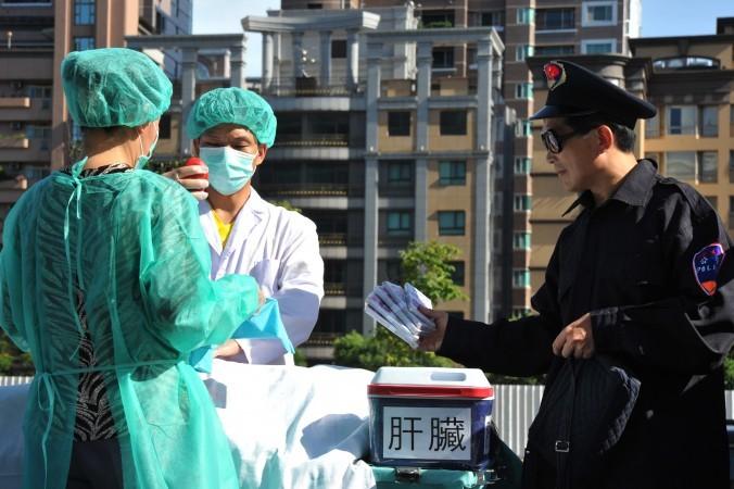 2014年7月20日、台湾の法輪功学習者は、臓器狩りのデモンストレーションを行い、問題を周知させようとしている。(Mandy Cheng/AFP/Getty Images)