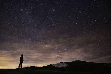 世界人口の3分の1は、光害の被害に遭っている。写真は2015年12月、イタリアのElva Hillで、星空を見上げる男性(MARCO BERTORELLO/AFP/Getty Images)