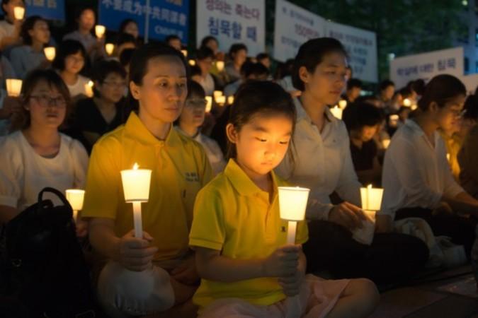法輪功学習者はソウルの清渓川で迫害の犠牲者への追悼と迫害停止を訴えるキャンドルナイト・イベントを行った。(金国煥/大紀元)