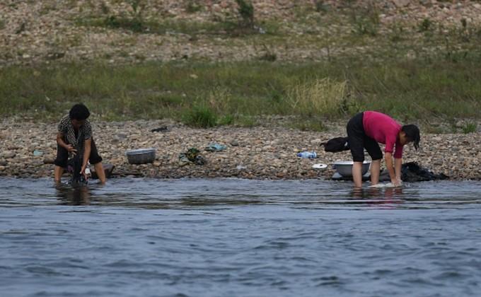 中朝国境の川で衣服を洗う北朝鮮の女性。9月11日撮影(GREG BAKER/AFP/Getty Images)