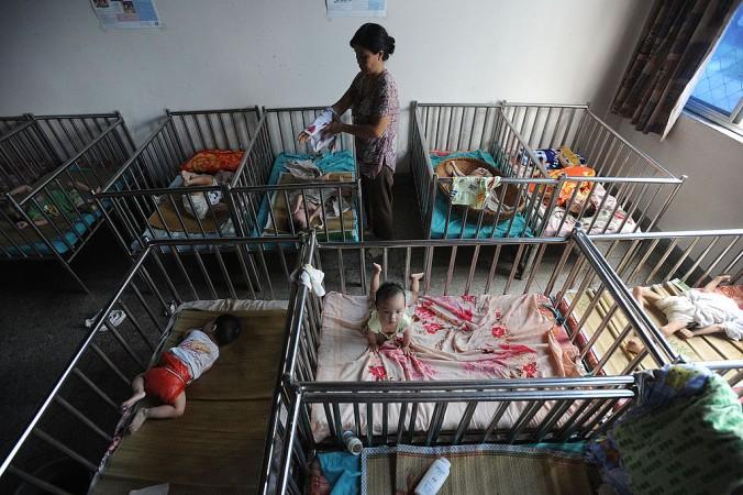 2009年、安徽省のある孤児院で赤ちゃんの世話をする女性(AFP/Getty Images)