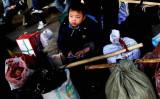 中国メディアによると、江蘇省常熟市のアパレル加工工場には、雲南省出身の16歳未満の児童労働者が多くみられる。2008年、北京に到着した出稼ぎ労働者の子ども。参考写真(Guang Niu/Getty Images)