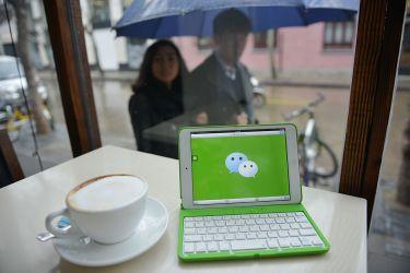 中国大手交流アプリWeChatは、中国の携帯電話番号で登録したユーザは、たとえ国外へ出ても、引き続き検閲されていることが、調査で明らかになった。写真は、WeChatのロゴが表示された小型パソコン(PETER PARKS/AFP/Getty Images)