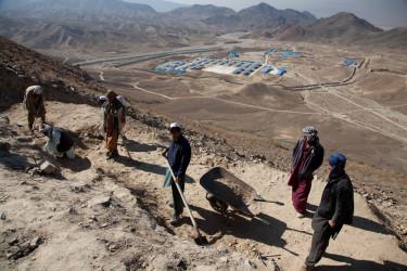 奥には、中国国有資源大手・中国冶金科工集団(MCC)がリース契約したメス・アイナク銅山の開発のためのテントが見える。手前は、仏教遺産の採掘を急ぐ考古学者たち。2011年撮影(Jerome Starkey/Flickr)
