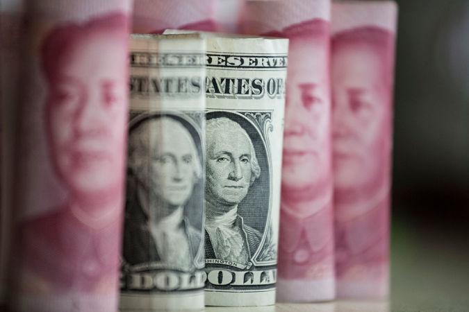 中国元を背景にした米ドル紙幣(FRED DUFOUR/AFP/Getty Images)