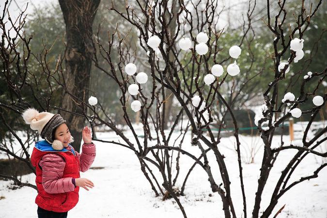 北京で2016年2月、旧正月の休暇シーズンに雪で遊ぶ女の子(Lintao Zhang/Getty Images)
