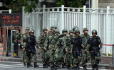 盾とこん棒で武装しパトロールする警官隊。後方には政府系とみられる建物の高いフェンスが見える。(PGOH CHAI HIN/AFP/Getty Images)
