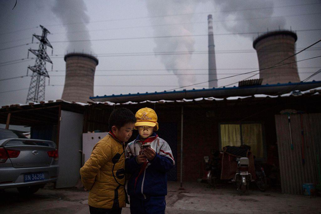 北京郊外に建てられた石炭発電所の近くにある住居で、スマートフォンを眺めている少年たち(Kevin Frayer/Getty Images)