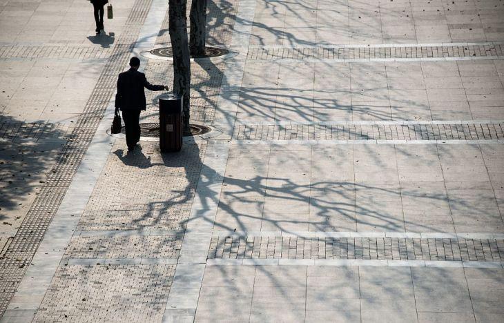2016年4月、上海の金融街で、路上のごみ箱にゴミを捨てる通勤中の男性(JOHANNES EISELE/AFP/Getty Images)
