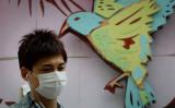 中国上海で、マスクを装着して歩く男性と、鳥のディスプレイ。中国当局の発表で5月に鳥インフルエンザA(H7N9)のヒト感染で37人が死亡していたことがわかった(GettyImages)