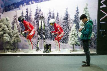 2月15日、北京で開かれた、雪山と技術の国際貿易の展示館で、スキーの展示の前に立つ男性(FRED DUFOUR/AFP/Getty Images)