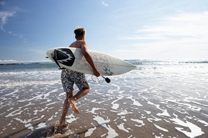 サーフィンで沖に出る男性(Fotolia)