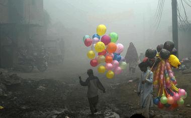 2016年12月、パキスタン北部ラホールで、濃いスモッグに見舞われる街の中を歩く風船売りの少年(ARIF ALI/AFP/Getty Images)