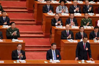 北京の人民大会堂で5日、全国人民代表大会の開幕式が開かれた。習近平国家主席(中央)と、スピーチを終え着席する李克強首相(向かって左)。(Lintao Zhang/Getty Images)