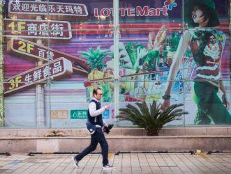 3月5日、杭州の韓国スーパーマーケット「ロッテ・マート」の前を通り過ぎる男性。(STR/AFP/Getty Images)