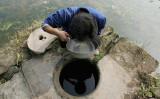 重慶の村で2004年11月、水質を調査するガン研究者(China Photos/Getty Images)