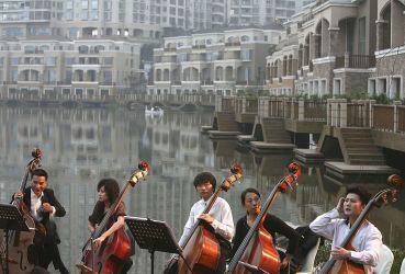 バブルが止まらない中国。十数の都市では不動産の売却制限を行うという。写真は2006年、重慶の超高級マンション群のオープニングセレモニーで演奏するチェリストたち(China Photos/Getty Images)