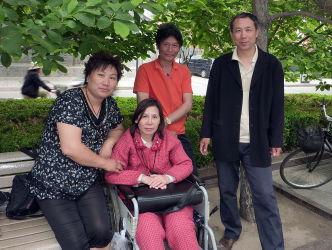 写真は2010年、北京の天安門広場近くで海外メディアの取材に応じる倪玉蘭さん(中央)、向かって右のスーツの男性は夫。支持者であり友人の2人。(ROBERT J. SAIGET/AFP/Getty Images)