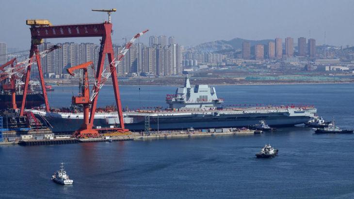 中国初の国産空母は40年前のロシア空母を完全複製し、欠点も同じだと専門家が指摘。4月26日、大連港から離岸する中国の新空母(STR/AFP/Getty Images)