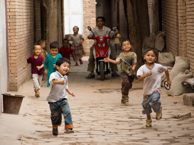 新疆ウイグル自治区カシュガルの街中を走る子供たち(Gusjer)