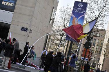 ベルギーのブリュッセルで2014年3月、中国・習近平国家主席の来訪に合わせて、神韻芸術団の広告を、中国国旗とベルギー国旗で隠そうとしている中国人、参考写真(GEORGES GOBET/AFP/Getty Images)