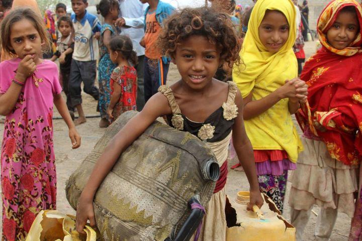 ユニセフによると、中東・北アフリカで子どもの貧困層は2,900万人に上るという。イエメンの女の子は、プラスチックの給水タンクを運ぶ(STRINGER/AFP/Getty Images)