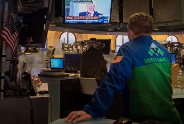 米国「パリ協定」を離脱へ、各国の反応は?会見する米トランプ大統領が映るスクリーンを見つめるトレーダ(BRYAN R. SMITH/AFP/Getty Images)