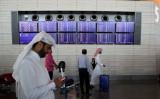 カタールのドーハにあるハマド国際空港で6月11日、フライト情報を掲示する電光掲示板と通行人(KARIM JAAFAR/AFP/Getty Images)