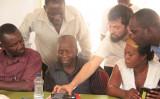 バーチャル・ファーマーズ・マーケット電子農作物取引アプリを試す人々(WFP)