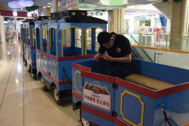 6月、北京市内ショッピングモールの玩具販売店近くで、機関車の形の乗り物でスマートフォンを見つめながら客を待つスタッフ(WANG ZHAO/AFP/Getty Images)