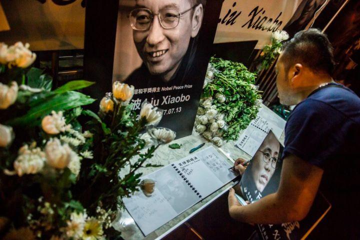7月13日、劉暁波氏の訃報を受けて、香港にある中国政府の出先機関「中央政府駐香港連絡弁公室」の建物近くに設置されたメッセージボード(ISAAC LAWRENCE/AFP/Getty Images)