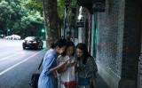 中国「ニコニコ動画」といわれる海外ドラマ配信サイトで大量に動画が削除された。上海市内でスマートフォンをのぞき込む若い女性たち(FRED DUFOUR/AFP/Getty Images)