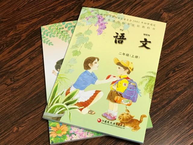 劉さんが見せてくれた中国の小学校教科書。カバーには母親が息子に赤いスカーフを着ける絵がある。(文亮/大紀元)