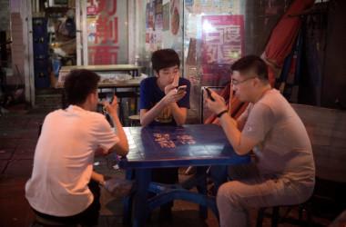 北京市内の屋台で5月、それぞれスマートフォンの画面を眺めながら料理を待つ男性たち(NICOLAS ASFOURI/AFP/Getty Images)